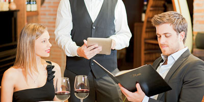 Restaurant scene with waiter taking orders on a tablet with online moblie Restaurant POS