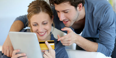 Couple making hotel booking on a tablet with Clock PMS Suite web reservation system