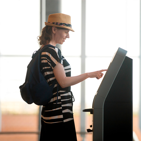 Woman checking in on her own at the hotel self-service kiosk of Clock Software