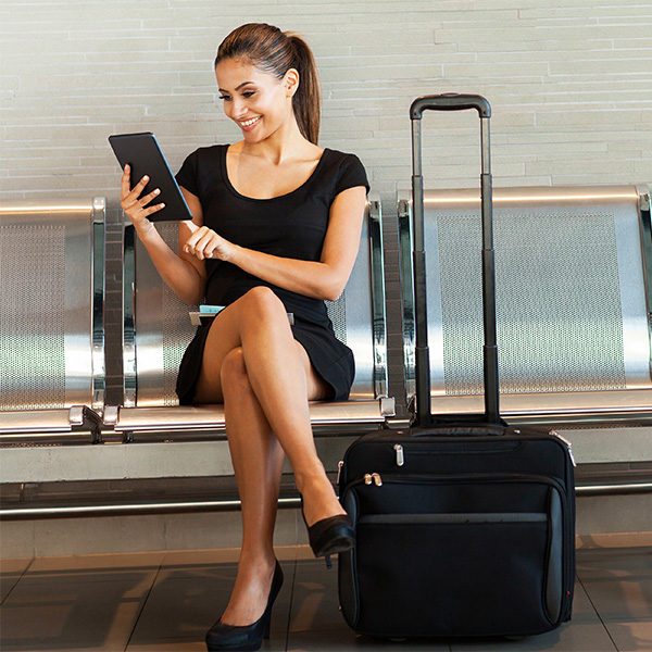 Woman with tablet using the hotel online check-in of Clock PMS